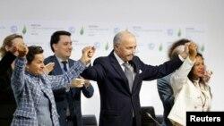 Waziri wa mambo ya nchi za nje wa Ufaransa Laurent Fabius, (kati), rais mteule wa COP21, na Christiana Figueres, kushoto, katibu mtendaji wa Umoja wa mataifa kwaajili ya mabadiliko ya hali ya hewa wakifurahia huko Le Bourget, France, Dec. 12, 2015.