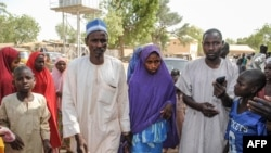 Msichana aliyeachiwa huru na Boko Haram akitembea na baba yake (kushoto) katika eneo la Dapchi Machi 21, 2018.