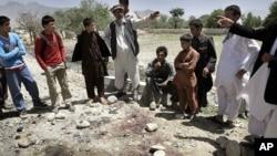 Dân Afghanistan đứng xung quanh các vết máu tại hiện trường sau một cuộc tấn công tự sát ở Kapisa, phía đông bắc thủ đô Kabul, Afghanistan