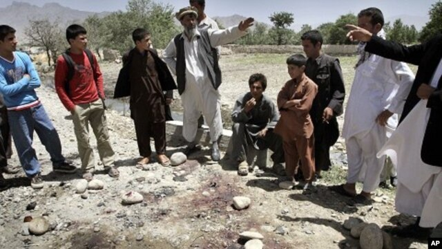Afghans stand around the bloodstains at the scene of a suicide attack in Kapisa, northeast of Kabul, Afghanistan, June 15, 2011