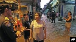 洪水涌入曼谷市中心,居民与警察交谈