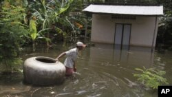 A man pulls a giant jar in flood waters on a street in Kandal province September 30, 2011. Some 141 people have died in Cambodia since Aug. 13 in the worst flooding along the Mekong River in 11 years after heavy rain swamped homes, washed away bridges and