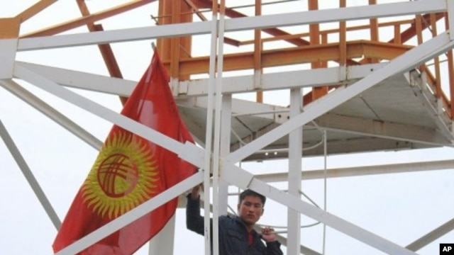 Flag-waving demonstrator climbing a tower at the Kyrgyz Defense Ministry, in  Bishkek, 14 Apr 2010