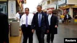 """2013年5月28日奧巴馬總統(右)和新澤西州長克里斯蒂(左)在新澤西州的""""澤西海岸""""木板道上巡察。"""