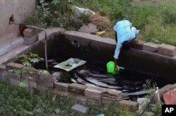 រូបឯកសារ៖ បុរសម្នាក់កំពុងដងទឹកពីអាងស៊ីម៉ង់ត៍នៅក្នុងទីក្រុង Bangalore ប្រទេសឥណ្ឌា។