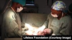 Bébé né par césarienne réalisée en urgence par un chirurgien généraliste (g) et une infirmière anesthésiste.