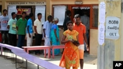 A Sri Lankan ethnic Tamil couple leaves after casting their vote as others line up to vote at a polling station during the northern provincial council election in Jaffna, Sept. 21, 2013.