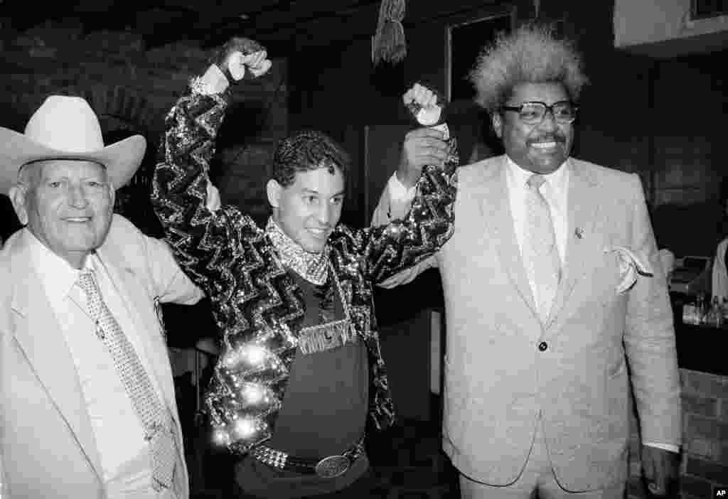 """Héctor """"Macho"""" Camacho en 1986 durante una conferencia de prensa en Nueva York sobre su conquista como campeón de peso pluma. En la foto aparece junto a Marty Cohen, izquierda, y su promotor Don King."""