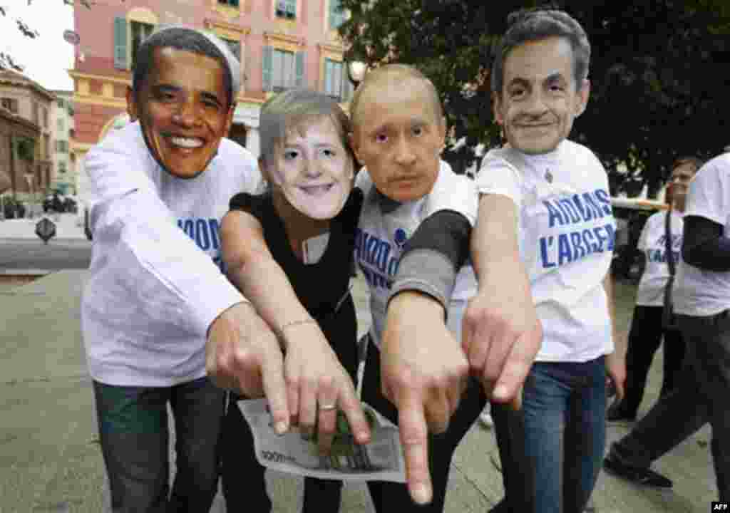 Anti-globalization members wearing masks, from left, of US President Barack Obama, German Chancellor Angela Merkel, Vladimir Putin Prime Minister of Russia and French President Nicolas Sarkozy demonstrate in Nice, southeastern France, against G20 summit