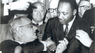 U.S. President Lyndon Johnson, left, and civil rights leader Martin Luther King Jr. shake hands at the Voting Rights Act's signing in the Capitol, Washington, August 6, 1965. (Creative Commons)