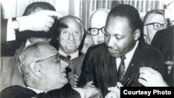 Martin Lyuter King (o'ngda) Saylov huquqlari to'g'risidagi qonunning qabul qilinishi munosabati bilan AQSh prezidenti Lindon Jonson bilan qo'l siqib ko'rishmoqda, 1965-yil, 6-avgust.