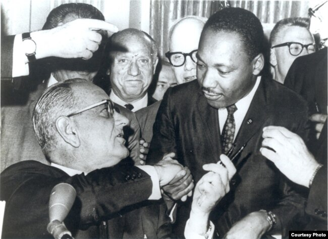 Photograph of President Lyndon Johnson signing the Voting Rights Act as Martin Luther King, Jr., with other civil rights leaders in Washington, DC, August 6, 1965.