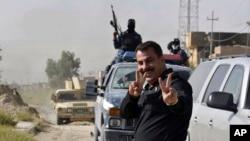 Pasukan keamanan Irak berpose saat merayakan pengambilalihan kota Fallujah di Irak dari kelompok Negara Islam (ISIS) (17/6).