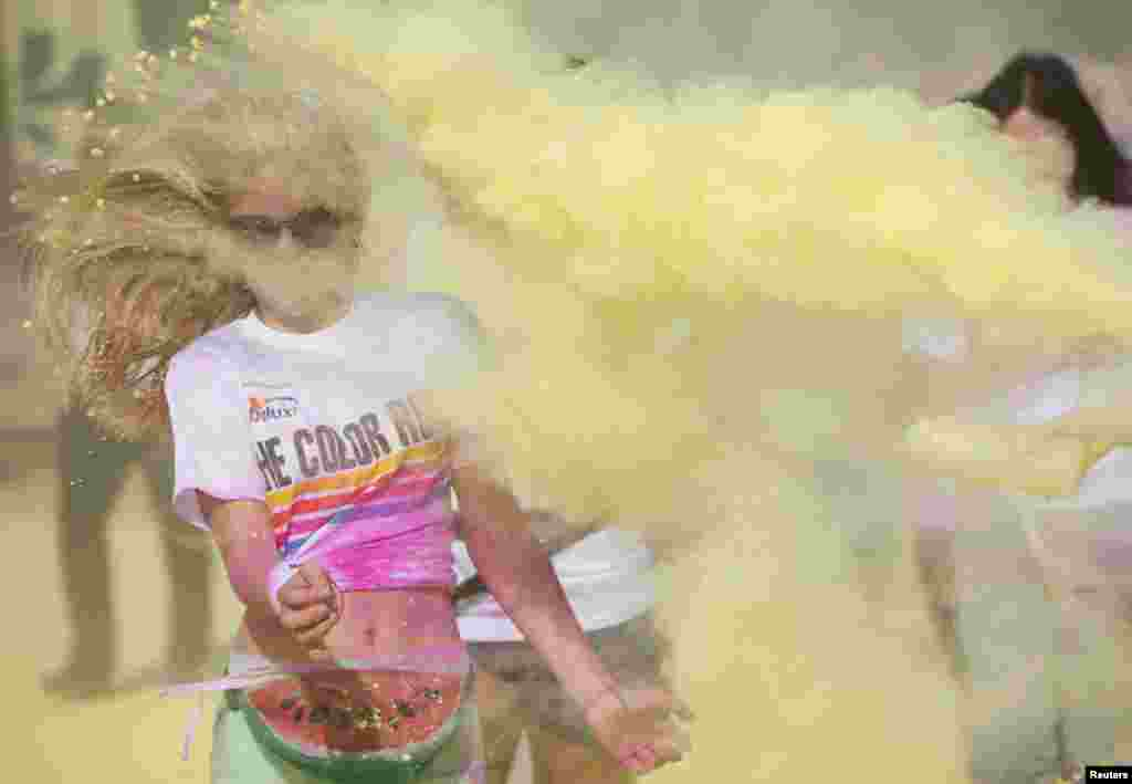 A woman is covered in paint as she takes part in a Color Run event in east London.