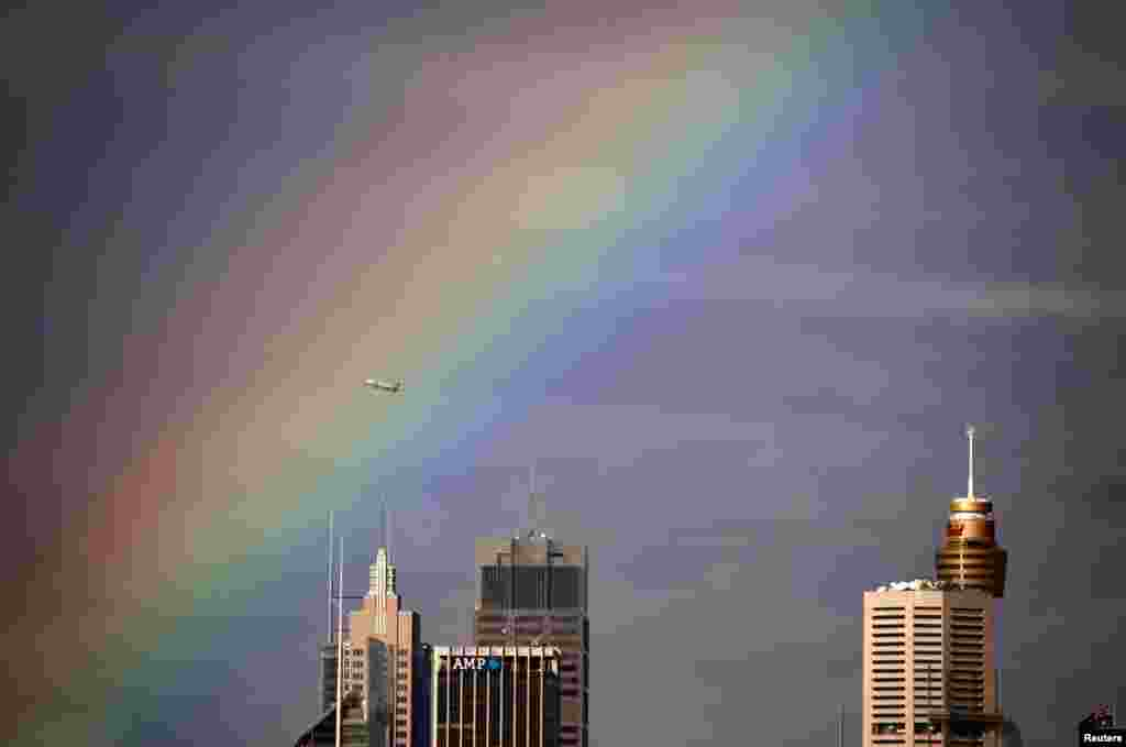 A Qantas Boeing 737 airplane flies through a rainbow above the central business district of Sydney, Australia.
