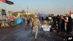 Seorang polisi tengah berpatroli di lokasi pemboman bunuh diri di distrik Dora, Selatan Baghdad (19/12). Dua buah ledakan bom dilaporkan mengguncang pasar di Tus Khormato, sebelah Utara Baghdad, Jumat pagi (20/12) dan menewaskan sedikitnya enam orang.