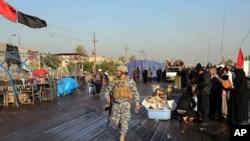 19일 경찰이 바그다드에서 자살폭탄 공격 현장을 순찰하고 있다