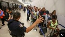 Des officiers de police surveillent la file d'attente du terminal 7 à l'aéroport de Los Angeles, le 28 août 2016.