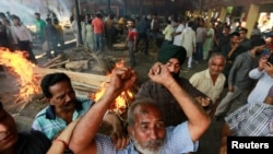 A man mourns next to the burning pyre of a family member who died after a train traveling at high speed ploughed through a crowd of people, at a cremation site in Amritsar, India, Oct. 20, 2018.