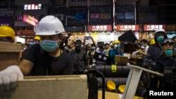 Para demonstran pro-demokrasi memasang blokade jalan baru dalam konfrontasi dengan polisi huru-hara distrik Mong Kok di Hong Kong (25/11).