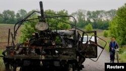 Seorang warga desa Oktyabrskoe, Ukraina Timur mendorong sepedanya melewati mobil lapis baja yang hancur akibat serangan pasukan pro-Rusia, 13 Mei 2014 (Foto: dok). Pemerintah Ukraina dilaporkan telah menghancurkan pangkalan militer pemberontak di luar kota Kramatorsk dan Slovyansk, Kamis (15/5).