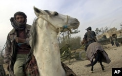 FILE - Militiamen loyal to Afghan warlord Abdul Rashid Dostum ride horses near Mazar-i-Sharif in northern Afghanistan, Nov. 28, 2001.