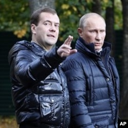 Russian President Dmitry Medvedev, left, gestures as he and Prime Minister Vladimir Putin walk at the presidential residence in Zavidovo, about 90 miles (150 kilometers) north of Moscow, Russia (File Photo).