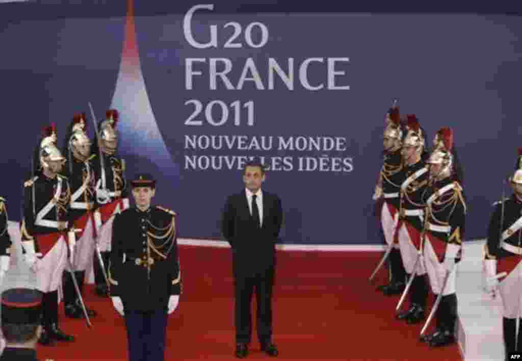 French President Nicolas Sarkozy, center, waits for China's President Hu Jintao during arrivals for the G20 summit in Cannes, France on Wednesday, Nov. 2, 2011. Greek Prime Minister George Papandreou was flying to the chic French Riviera resort of Cannes