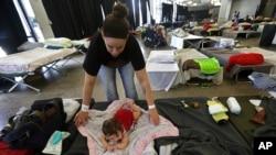 عارضی پناہ گاہ میں ایک خاتون اپنی بچی کی دیکھ بھال کر رہی ہیں