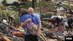 Seorang lelaki menyelamatkan seorang anak perempuan yang terkurung di bawah reruntuhan rumahnya yang dirobohkan tornado di Joplin, Missouri (23/5).