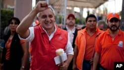 Otto Perez Molina, of the Patriotic Party, greets supporters as he campaigns in Guatemala City, Sunday, Oct. 30, 2011. (AP Photo/Rodrigo Abd)
