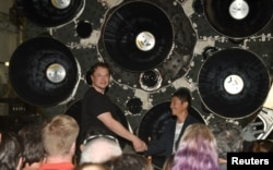 FILE - SpaceX CEO Elon Musk (L) shakes hands with Japanese billionaire Yusaku Maezawa during a press conference about being the first SpaceX private passenger to circle the moon aboard SpaceX's BFR launch vehicle, in Hawthorne, California September 17, 2020