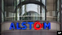 FILE - The company logo of Alstom is shown at the headquarters of the leading global maker of high-speed trains, power plants and grids, in Levallois-Perret, outside Paris, France, April 30, 2014. U.S Justice Department officials on Dec. 22, 2014, announced the French power and transportation company has agreed to pay $772 million in penalties to resolve allegations that it bribed government officials in multiple foreign countries and would plead guilty to violating the Foreign Corrupt Practices Act.