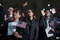 "Participants in a naturalization ceremony raise their hands to take the ""Oath of Allegiance"" at an event attended by President Barack Obama at the National Archives in Washington, Dec. 15, 2015."