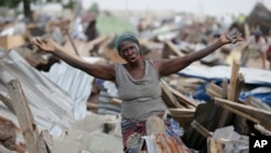 FILE - A woman gestures in front of a demolished house in Otodo-Gbame waterfront in Lagos Nigeria. March 18, 2017.