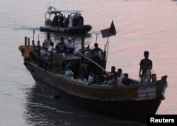 FILE - Rohingya refugees, who were intercepted by Malaysian Maritime Enforcement Agency off Langkawi island, are escorted in their boat as they are handed over to immigration authorities, at the Kuala Kedah ferry jetty in Malaysia, April 3, 2018.
