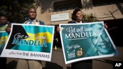 A group of wellwishers hold up get-well placards outside the entrance to the Mediclinic Heart Hospital where former South African President Nelson Mandela is being treated in Pretoria, June 16, 2013.