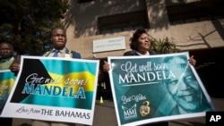 曼德拉的支持者站在曼德拉接受治療的醫院外,舉著希望他康復的標語牌。