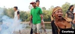 Sekelompok Masyarakat Adat Laman Kinipan dengan latar belakang sungai dan hutan. Foto Aliansi Masyarakat Adat Nusantara (AMAN)