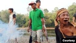 Sekelompok Masyarakat Adat Laman Kinipan dengan latar belakang sungai dan hutan. (Foto: Aliansi Masyarakat Adat Nusantara (AMAN)).