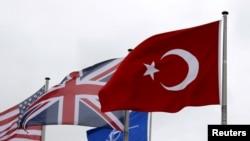 Bendera Turki (kanan) berkibar antara lain bendera anggota NATO selama Dewan Atlantik Utara (NAC) di markas Aliansi di Brussel, Belgia, 28 Juli 2015. (Foto: REUTERS/Francois Lenoir)
