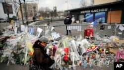 Une femme allume une bougie devant le supermarché juif où le terroriste Amédy Coulibaly a exécuté quatre hommes, à Paris, le 20 janvier 2015.