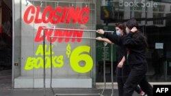 Para pekerja mendorong troli melewati sebuah toko kosong di distrik pusat bisnis Melbourne, 3 Agustus 2020 setelah negara bagian tersebut mengumumkan pembatasan baru di tengah pandemi Covid-19.