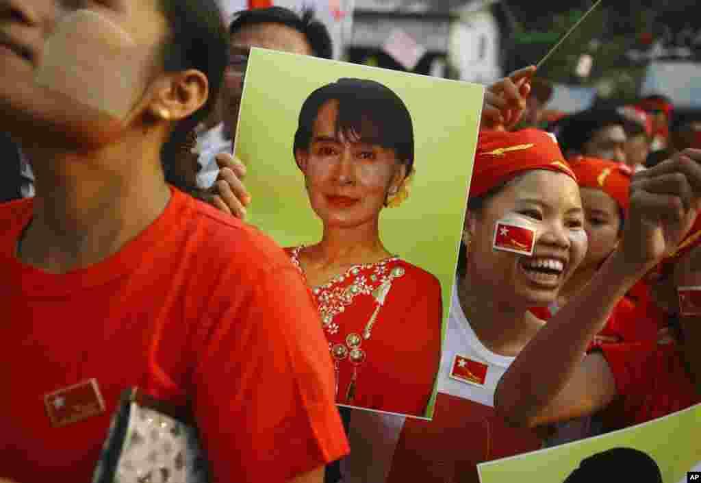 支持者们4月1日在仰光缅甸全国民主联盟总部前手持昂山素季的肖像,注视着反映选情的屏幕