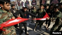 Iraqi Shi'ite protesters tear up a Turkish flag during a rally against Turkey's military presence in northern Iraq, in Basra, Iraq, Oct. 9, 2016.