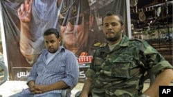 Motasin Younis, left, and Mohammed Hamed Younis, right, son and nepheiw of Libyan rebels' slain military chief Abdel-Fattah Younis seen during a interview in rebel-held Benghazi, Libya, Aug. 1, 2011