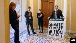 Joe Mendelson, el jefe de la mayoría del consejo del clima, parte de la Comisión de Medio Ambiente del Senado, y otros funcionarios, reciben a los participantes de una sesión especial sobre el cambio climático.
