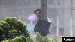 Um homem agarra-se a um poste durante a passagem do tufão Hato em Hong Kong, China, 23 de Agosto, 2017