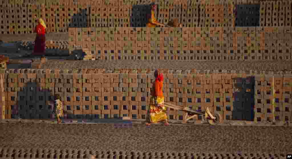 Para pekerja perempuan memindahkan batu bata dengan menggunakan kereta yang ditarik tangan di pinggiran kota Jammu, India.