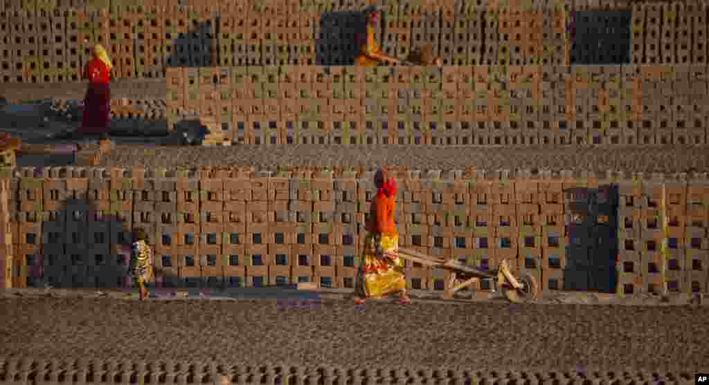 Laborers transport bricks on hand carts at a brick kiln factory on the outskirts of Jammu, India.